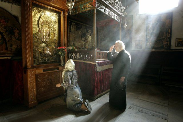 Photo: A Greek Orthodox monk and another worshipper pray next ... / LJWorld.com
