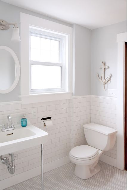 This dreamy Victorian-style bathroom is painted in BEHR Curio off-white, which is paired with a blue accent and white-washed anchor for a beachy feel. The white subway tile and pedestal sink tie in this lovely space.