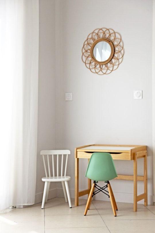 """Pour les petits... Une maison à la déco métissée qui nous fait voyager Dans le salon, un petit coin est dédié aux enfants. Sous un miroir """"soleil"""", on y trouve deux adorables chaises design (l'une de style Windsor et l'autre copiant l'iconique modèle de Charles et Ray Eames). Détail subtil : la couleur de l'une fait écho à la teinte vert d'eau de la cuisine."""