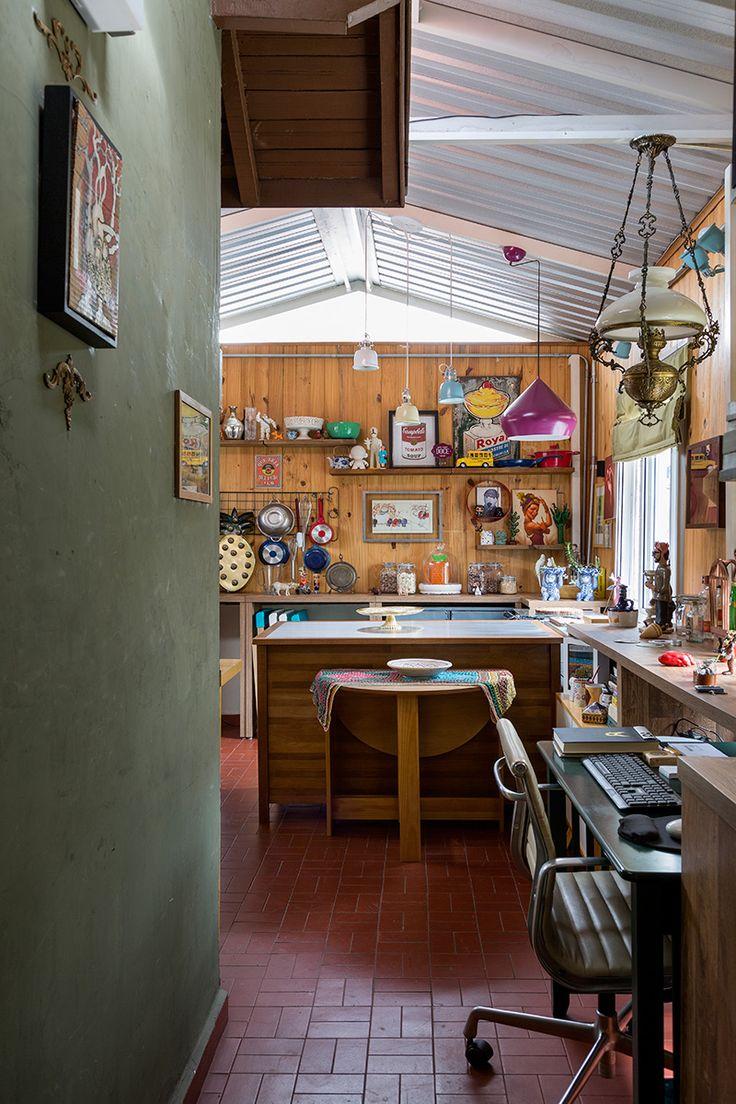 Casa pequena, casa charmosa, cozinha com revestimento em madeira, quadros e muitos detalhes.
