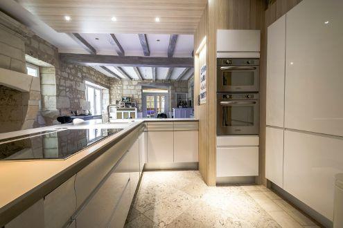 Une cuisine design en laque brillante blanche aménagée par le magasin Arthur Bonnet de Chambray-lès-Tours dans une maison en pierres. Un beau contraste des styles !