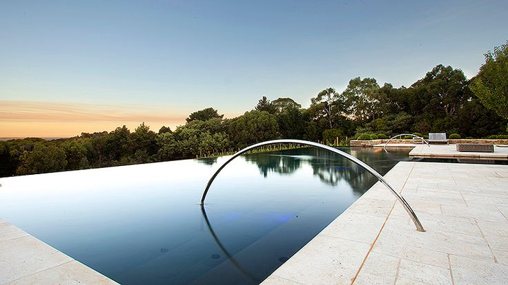 Pool With Infinity Edge And Long Curved Stainless Steel Hand Rail Pinned To Pool Design By