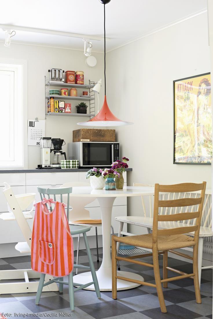"""Der Blickfang dieser Retro-Wohnküche ist die rote dänische Klassikerleuchte """"Semi"""" des Labels Gubi. Die unterschiedlichen Stühle sind weitere Hingucker, die den schlichten """"Tulip""""-Tisch optimal zur Geltung bringen. #roomido Mehr auf roomido.com"""