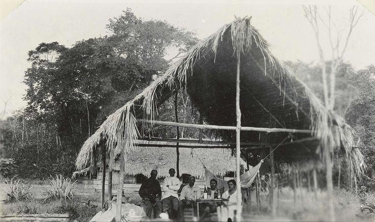 Anonymous | Het echtpaar Brouwers met vrienden in een hut, Anonymous, 1911 - 1932 | Het echtpaar Brouwers met vrienden in een grote open hut in Suriname, het paar rechts op de foto is het echtpaar Brouwers.