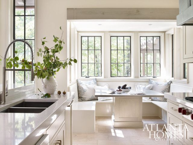 A glazed finish on the banquette lends an ethereal quality to the kitchen's breakfast nook. Designer Richard Tubb painted the window muntins dark to frame the home's scenic views. Pillows from Bungalow Classic.
