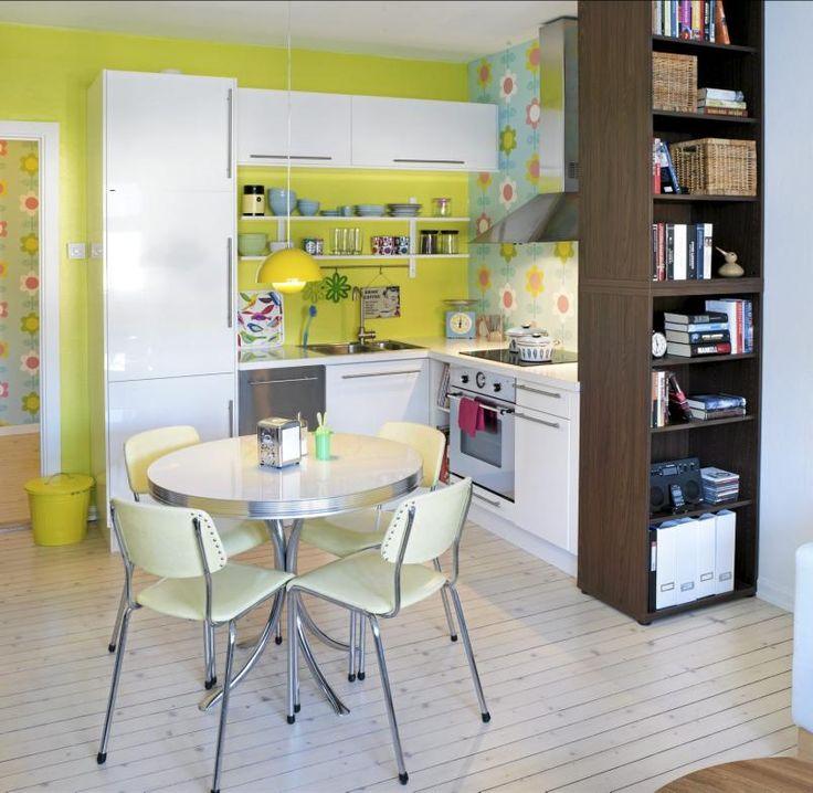 Dette retropregede kjøkkenet er som et friskt pust. Den ene veggen er malt i en sterk gulgrønn farge, mens den andre halvdelen er dekket med en blomstrete tapet, kjøkkeninnredningen er derimot holdt enkelt i hvitt. Pastellgrønne stoler står rundt kjøkkenbordet, mens en mørk trehylle bryter opp det sukkersøte.