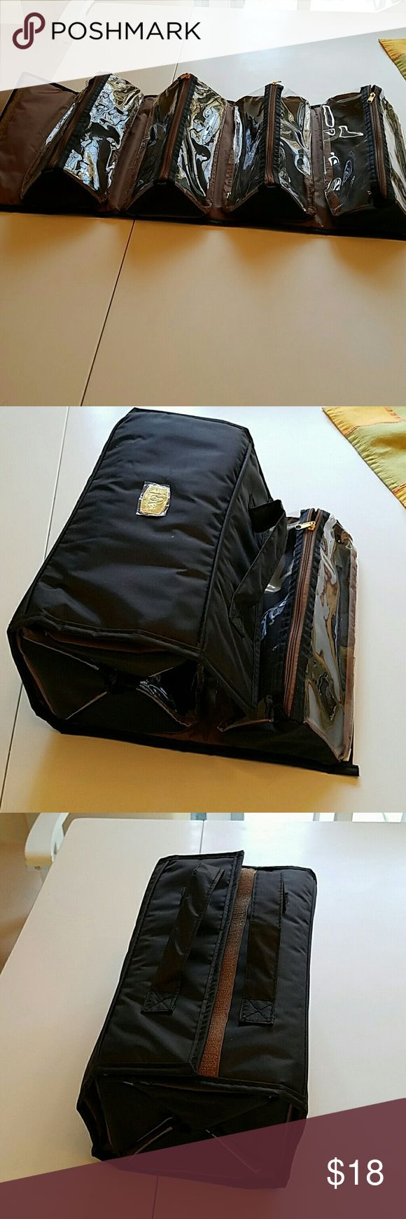 Travel bundle case Amazing@ it's perfect for traveling! 4 your makeup ,hair stuff, sm stuff, etc!! U have 4  zipped compartment and then it rolls into a square and velcros closed with handle on top. Never used it Nwot.. still has plastic film over opening.. it is a black like canvas material which you can easily wipe down,  perfect to put in your suitcase with everything in it and 4zip compartments! When it is totally open across it measures 22 by 11 as you see in picture one..got at bed…