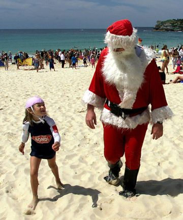 Santa on beach in New Zealand - it's summer Down Under Christmas-time and New Year! #santa #NewZealand