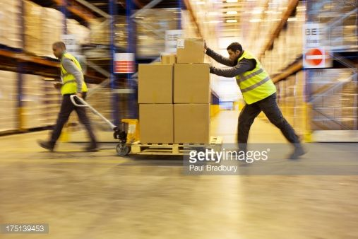 Stock Photo : Workers carting boxes in warehouse