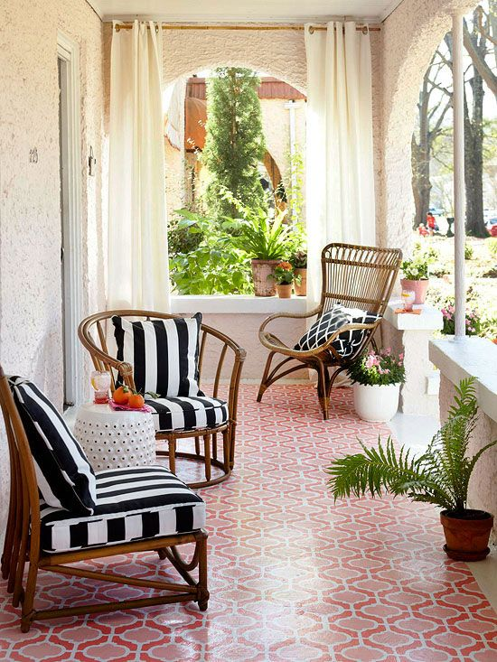 Outdoor Living :On the front porch, black-and-white striped outdoor fabrics elevate the style of the chairs, including two rattan chairs the homeowner scooped up from the side of the road. Easy, breezy curtains lend shade and privacy. The floor was stenciled to look like expensive Spanish tile.