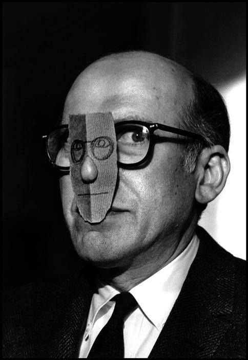 ¤ Saul Steinberg wearing a nose mask of his own face. From the Mask Series with Saul Steinberg, 1959. Photograph by Inge Morath © The Inge Morath Foundation/MAGNUM PHOTOS.