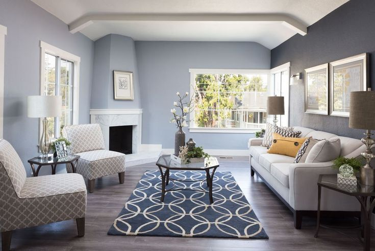 Blue-grey living room with patterned chairs, carpet and pastel decor. #painters #decorators #builders #tilers #London #livingroom #pastel