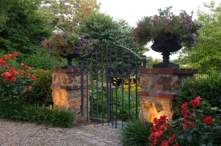 Enmarcando la entrada con unas copas de piedra con macizos de flores.