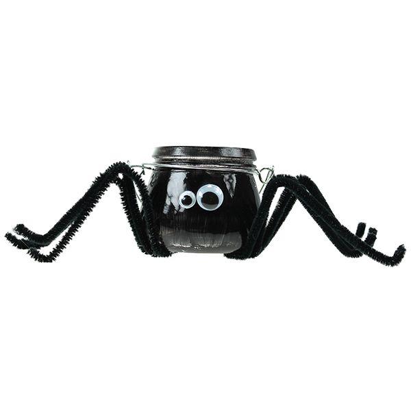 Mustalla lasimaalilla maalattu lyhty, joka on koristeltu liikuvilla silmillä ja askartelupunoksista valmistetuilla jaloilla.