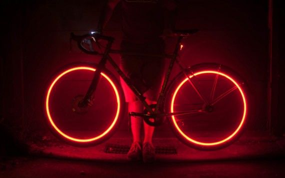 The Project Aura safety lighting system illuminates the wheels of the bicycle for side visibility, and also indicates the rider's intent through change of light color: red for slowing down, white for speeding up. | velojoy.com