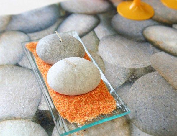 A chaque bout de la table, voici une petite composition réalisée avec une petite assiette en verre, du sable décoratif et des petites bougies en forme de... galets bien-sûr !