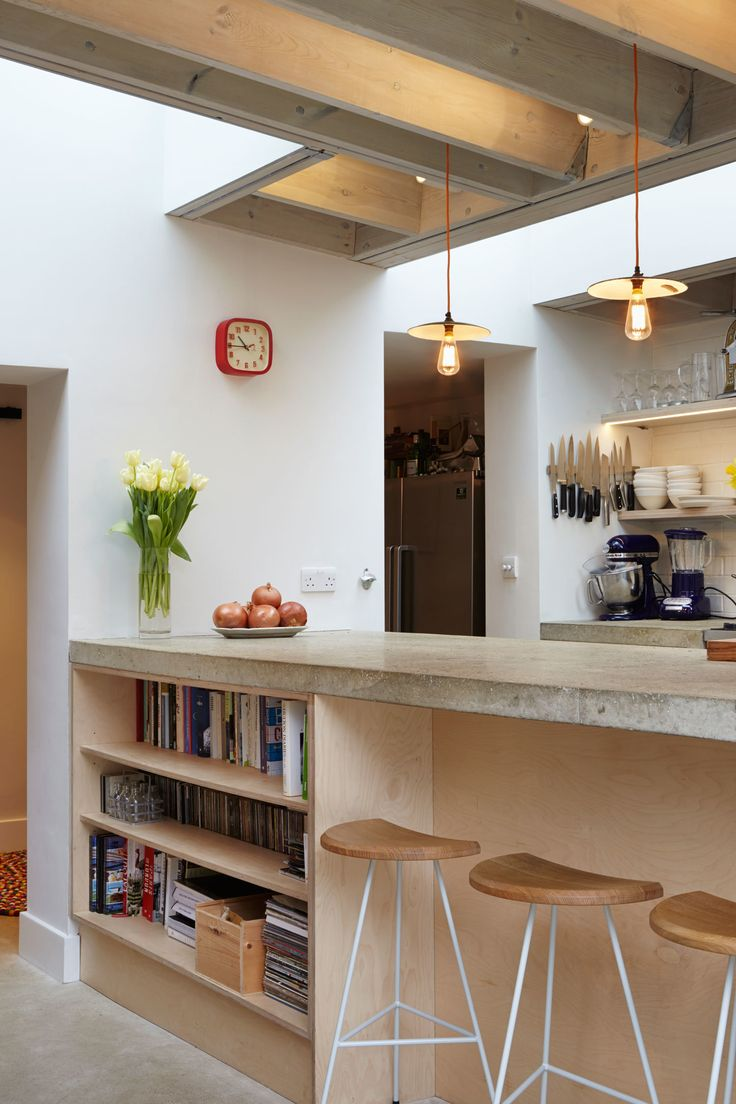 The architecture firm's in-house joinery company, Fraher and Co, incorporated storage spaces throughout the home. Beneath the kitchen bar, a birch plywood bookcase holds the chef's collection of cookbooks and music. Shelves flanking the oven also store and showcase dishes, glasses, and wine bottles.