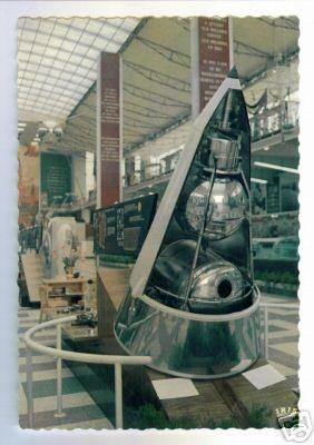 The above is a postcard from Brussels   World Fair 1958, showing a model of the   Sputnik-2 nose cone. Note - Laika's tiny   pressurized capsule (see round window)   was designed to operate for one week.  I remember this exhibit distinctly