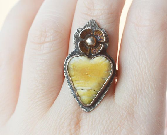 This is a sterling silver and natural baltic amber ring made in my studio. The butterscoch amber is heart shaped and has nice vertically ribbed texture. This shape and colour amber is very rare! It has been set into hammered rustic sterling setting with a large 4 petal flower on top. The
