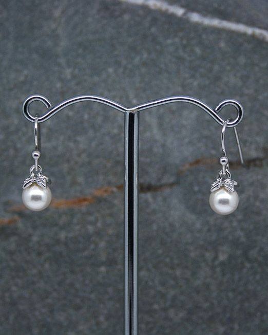 Swarovski pearl drop earrings.  A delightful pair of pearl drop earrings, suitable for any occasion.  The 6mm pearls are capped with a very simple four leaf mounts and are secured on silver plated hook fittings.  The overall length of the earrings is 18mm from the top of the fitting.  The mounts are created in brass and rhodium plated.  We can supply these earrings in multiples for bridesmaids and groups etc, please enquire.  All of our jewellery comes in blue or silver box with ribbon...