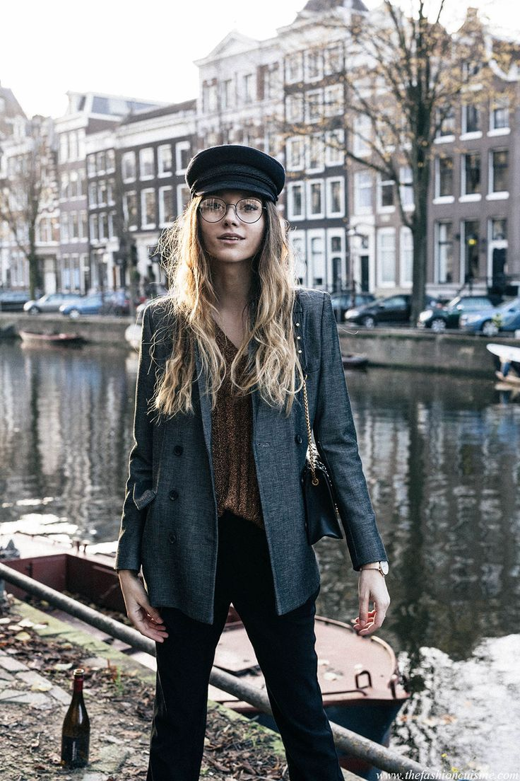 Fashion blogger Beatrice Gutu wearing metallic sweater trend with sailor cap and grey classic blazer in Amsterdam