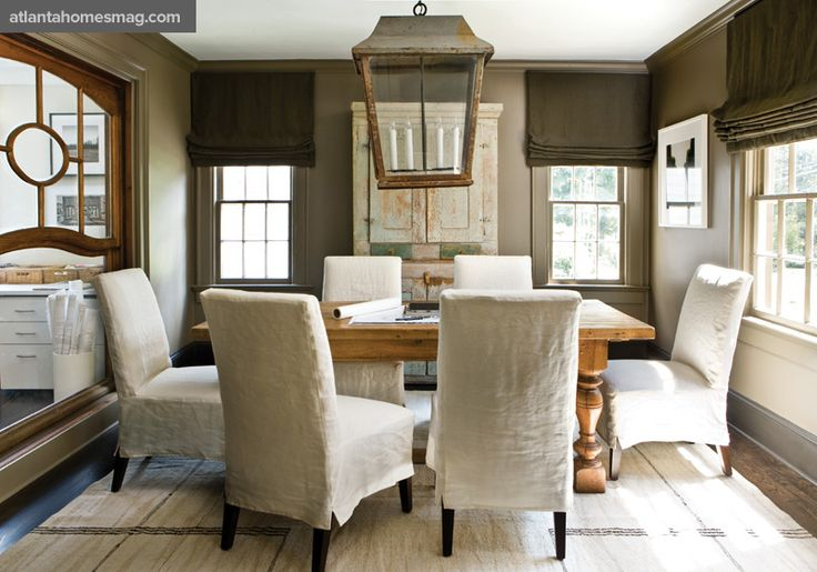 In the conference room, slipcovered Parson chairs and a flatweave rug from Sullivan Fine Rugs create an interesting contrast to the space's earthier tones, from the walls, painted in Satchel by Benjamin Moore, to an overscale patinaed lantern and French oak table.: Dining Rooms, Wall Colors, Idea, Romans Shades, Lights Fixtures, Slipcovers, House, Chairs Covers, Lanterns