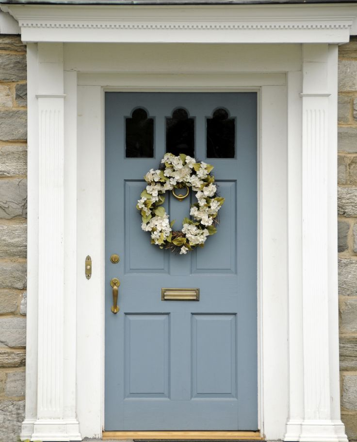 The front door has a brass lock, door handle, mail slot, and door knocker, a white door casing with a brass plated doorbell.