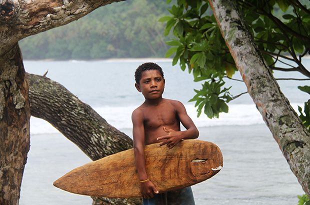 Paga Hill Estate, Paga Hill Development Company a young local surfer in papua new guinea holding his wooden splinter surfboard shaped like a modern surfboard