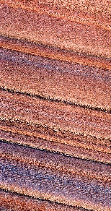Mars ~ This false-color image of the north polar layered deposits has been processed to emphasize color variations, showing that the color as well as texture/ morphology varies from layer to layer. Some of the color variations may be caused by small amounts of water frost on the surface, or they may be due to variations in dust composition within the layered deposits. Such changes may have been caused by volcanic eruptions or local weather phenomena when the layers were deposited.