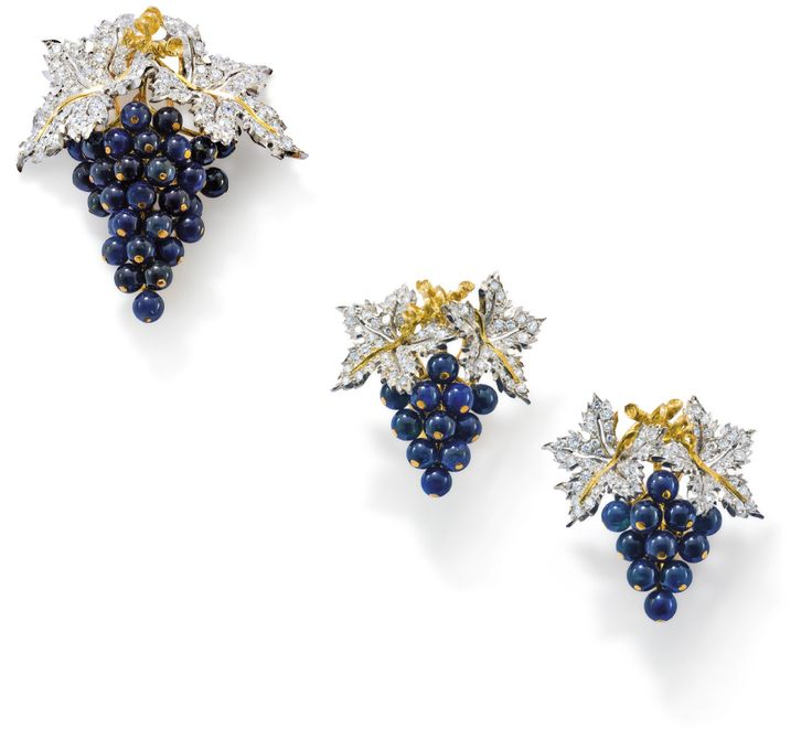 A suite of diamond and sapphire jewellery, by Buccellati ;Comprising a brooch realistically modelled as a bunch of grapes, the vine leaves pavéset with brilliant-cut diamonds from which cascade grapes of sapphire beads, pin-clip fitting to rear, length 4.8 cm, signed 'Buccellati', numbered N2284; accompanied by a pair of earclips of similar design, length 2.8 cm, signed 'Buccellati', numbered N2285. With grey leather box signed 'Gianmaria Buccellati'.