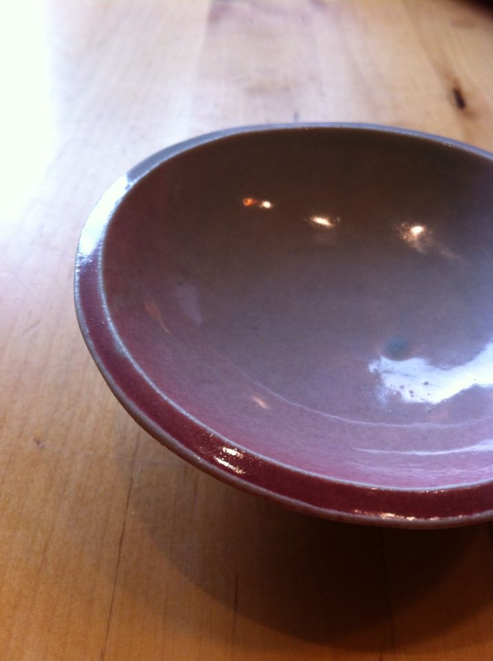 Pink blush on hand thrown green pottery dish