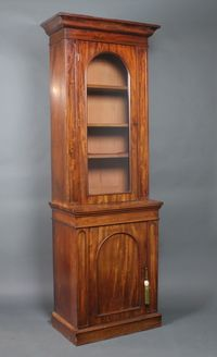 Lot No 972 A Victorian mahogany bookcase on cabinet the upper section with moulded cornice, fitted shelves enclosed by an arched panelled door, the base fitted a cupboard, raised on a platform base, sold £540