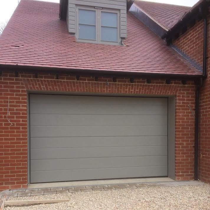 Pair of Novoferm iso 45 Large Rib Sectional Garage Doors in Woodgrain RAL 7030, installed in East Hanney Our second development for this property developer, we installed a pair of Novoferm iso45 Large Rib Sectional Garage Doors in RAL 7030 to match the window frames. Door Specification: iso45 Insulated, Automated Sectional Garage Door by Novoferm Large …