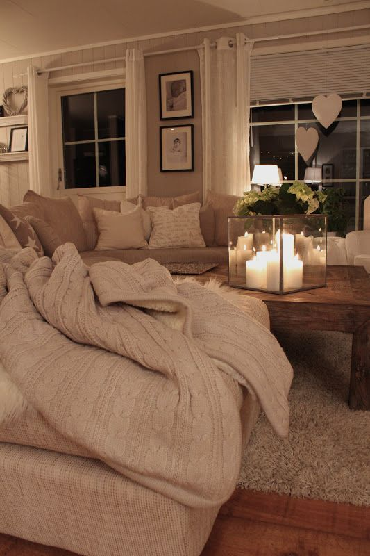I love the square glass candle holder - Cosy room with wood and neutral colours and white candles with clear glass Creams and browns and beiges Corner sofa around coffee table Full length thin curtains Cotton throws to mix with fur throws Low wooden coffee table