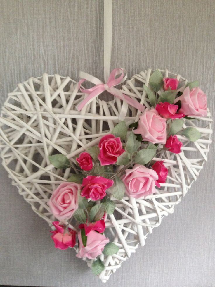 Wicker heart that has been decorated using foam roses.