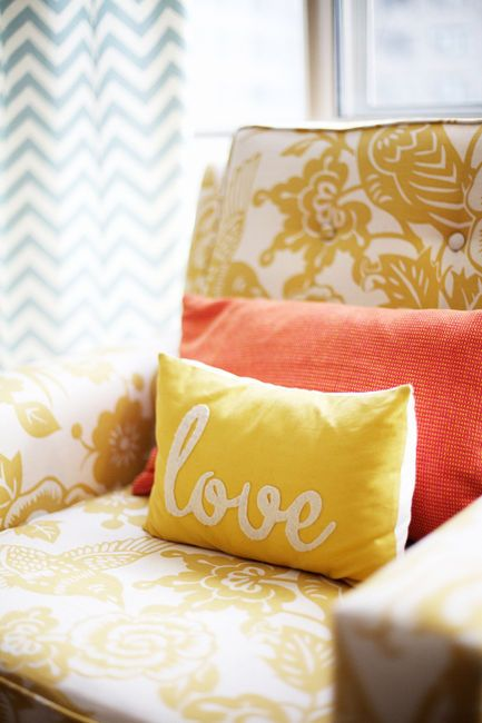 I love everything about this picture.  The chevron curtains, yellow vintage chair, and the cute pillows!