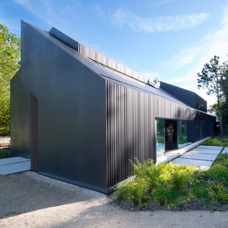 Four separate volumes fit together to form this villa in the Netherlands, designed by Studio Prototype as an interpretation of typical black barns