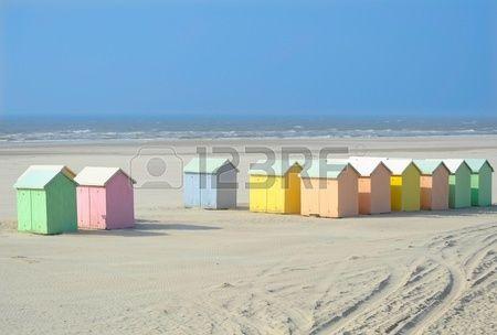 Een zandstrand met pastelkleurige houten hutten Stockfoto