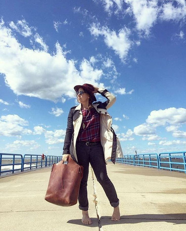 Fall fashion inspiration with her hat, large leather bag accessory, cuffed jeans, and checkered top... @bajalyn carries her leather market tote at the beach pier on Lake Michigan. Shop this leather tote at www.urbansouthern.com