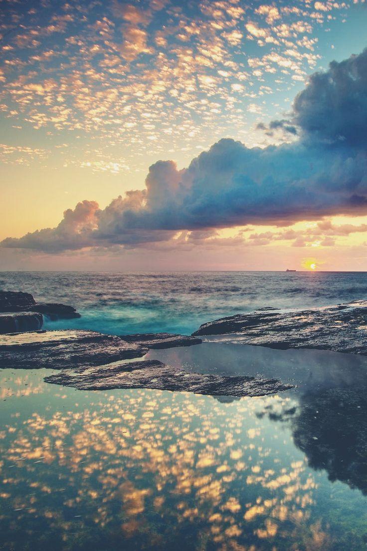 gespiegelte Wolken im Meer. Sonnenuntergang am Strand.