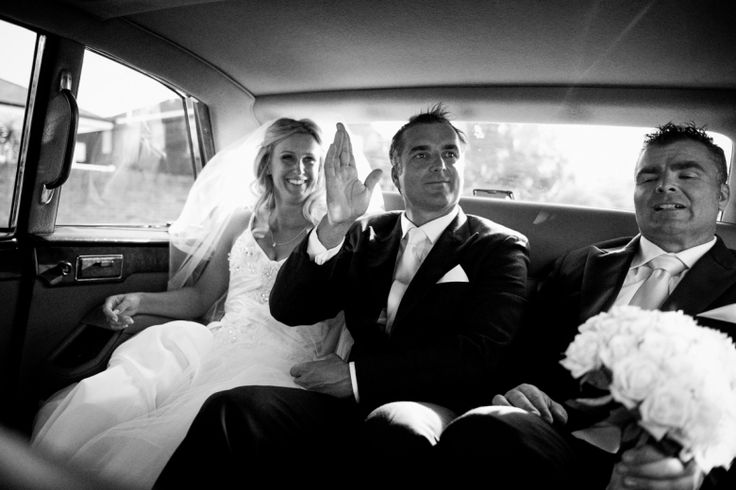 Bride, groom and best man in the back of the bridal car at a wedding at home at Milford beach, Auckland. Black and White.  beguiling fine art family photographs for the walls of the most discerning clients homes. We specialise in wedding and family portrait photography, and supply prints on the highest quality media, framed in beautiful conservation standard frames. We are a high end studio located in the beautiful city of Auckland, New Zealand.