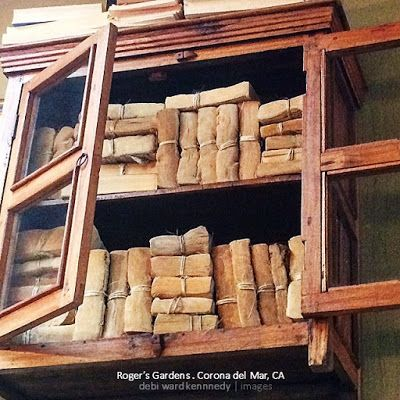 tips from a visual stylist:  make NEW books look OLD using.... coffee???! from Debi Ward Kennedy on homewardFOUNDdecor.com (photo taken at Roger's Gardens, these faux old books not created by me)