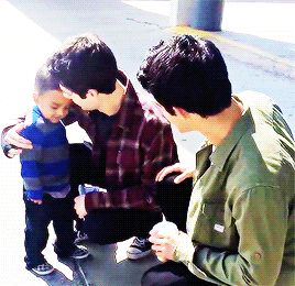 Dylan O'Brien and Tyler Posey with a fan on set