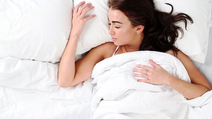 Attractive young woman waking up in bed at home - HD stock video clip