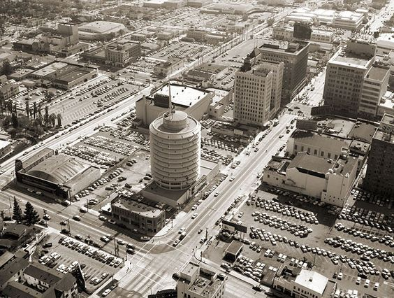 """This aerial view of the Capital Records building near Hollywood and Vine (this photo is looking south) was taken in 1956, the year that building opened. What surprised me a little was how the area was already a sea of parking lots. LA's freeway system was just getting going in the 50s so I don't think of LA being quite so car-dependent at this time. The building to the right was The El Capitan Theatre and was where Richard Nixon delivered his famous """"Checkers speech"""" on September 23, 1952."""