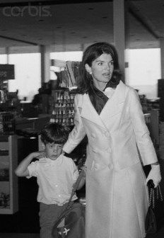Mrs. kennedy leading her son John through a gift shop in the New York airport named for her late husband, before boarding their plane to Hawaii.
