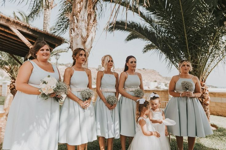 Bridesmaids were standing under the palm shades in light grey knee-length dresses with twee straps and cute white belts