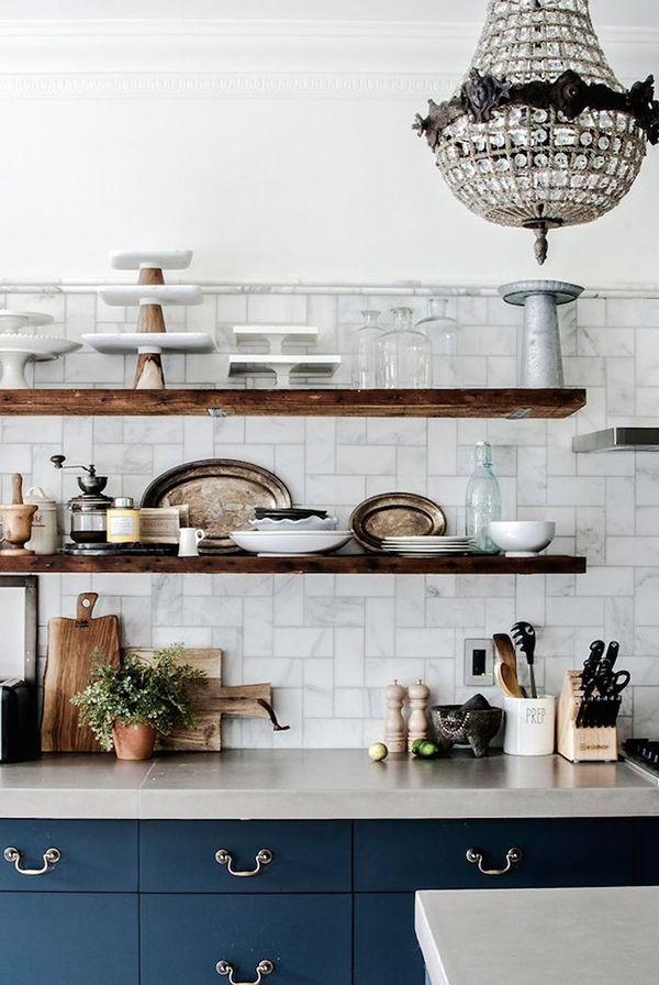 blue cabinets + gray square marble tile + concrete counters + chandelier + open shelves