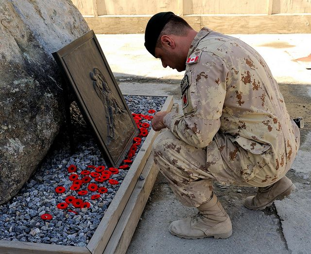 Remembrance in Afghanistan 2013   Sergeant Martin Veilleux pays his respects to the fallen by placing a poppy on the memorial honouring Canadians who died in Afghanistan in front of Canada House at Camp Phoenix, Kabul on 11 November, 2013. #StrongProudReady