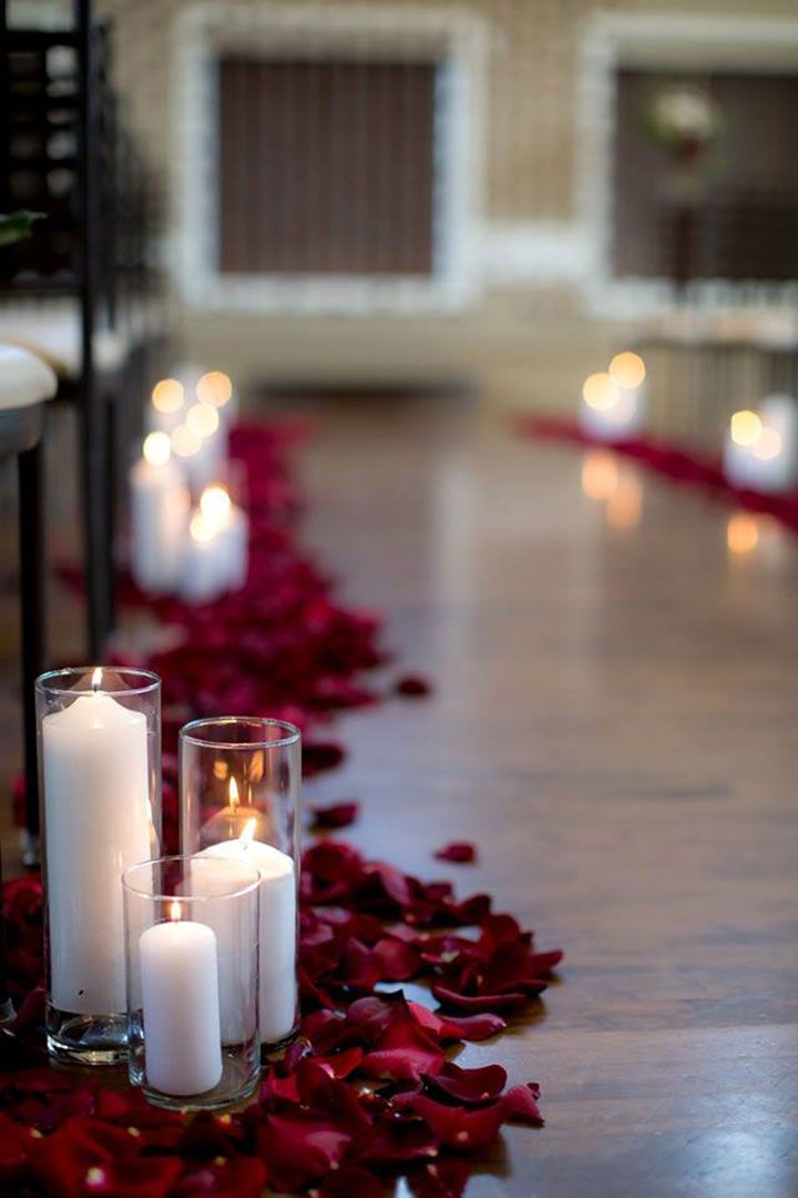 Deep red rose petals and white pillar candles in glass hurricanes lined the…